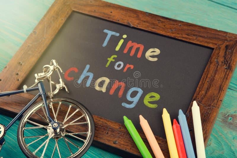 Time för ändring - som är skriftlig med färgpennor på den svart tavlan arkivfoton