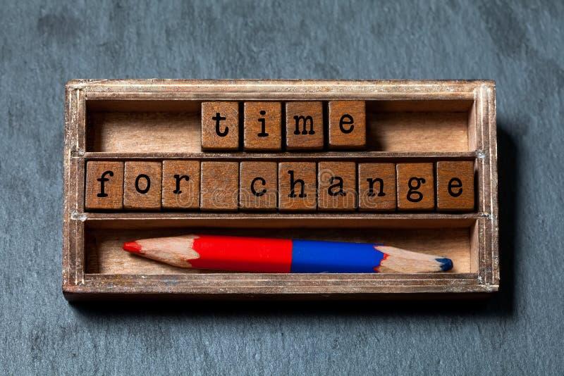 Time för ändringscitationstecken Tappningasken, träkuber med bokstäver för gammal stil, färgrika röda blått ritar Texturerad grå  royaltyfri foto