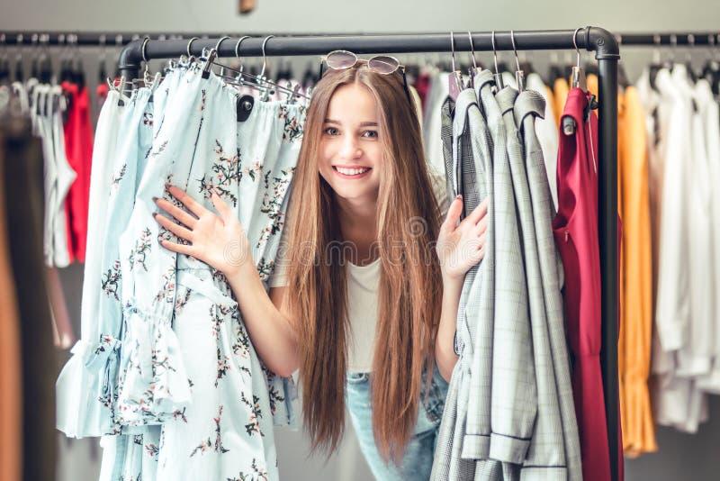 Time för att shoppa! Lyckligt anseende för ung kvinna nära kläderkuggen Ståenden av den långhåriga brunetten ler i lagret royaltyfri foto