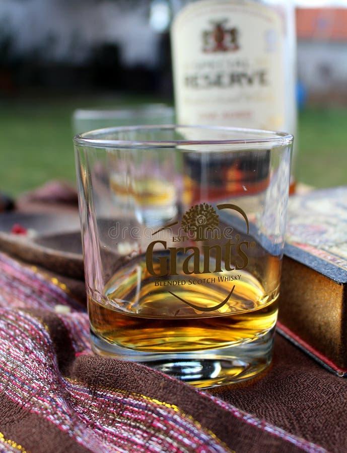 Time för drink - ett exponeringsglas av whisky på en trädgårds- tabell royaltyfri bild