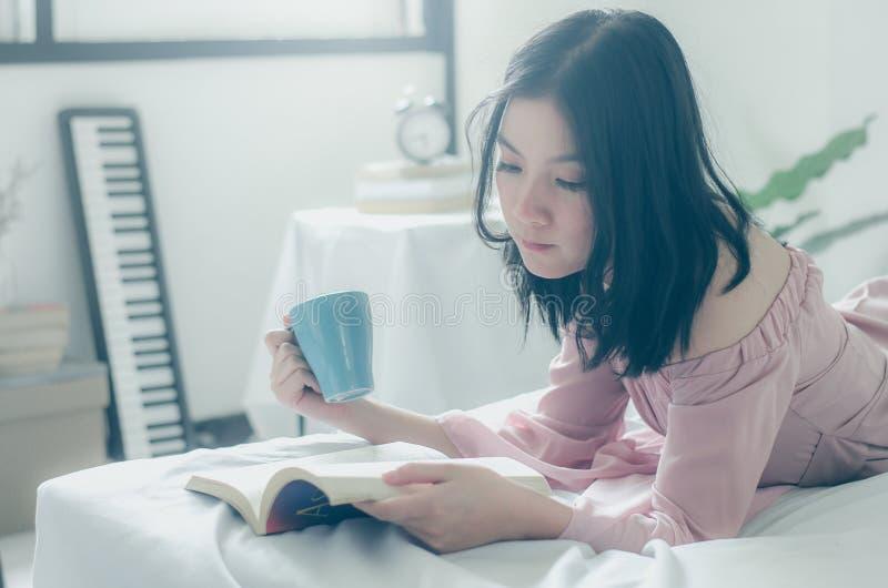 Time f?r mig Komfort och avkoppling Nätt ung asiatisk kvinna som dricker te eller kaffe och läsebok, medan sova royaltyfri foto