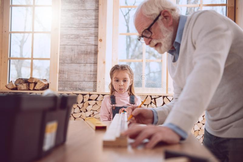Serious smart girl being in the workshop. Time with family. Serious smart girl looking at her grandfather at work while being in the workshop royalty free stock photography