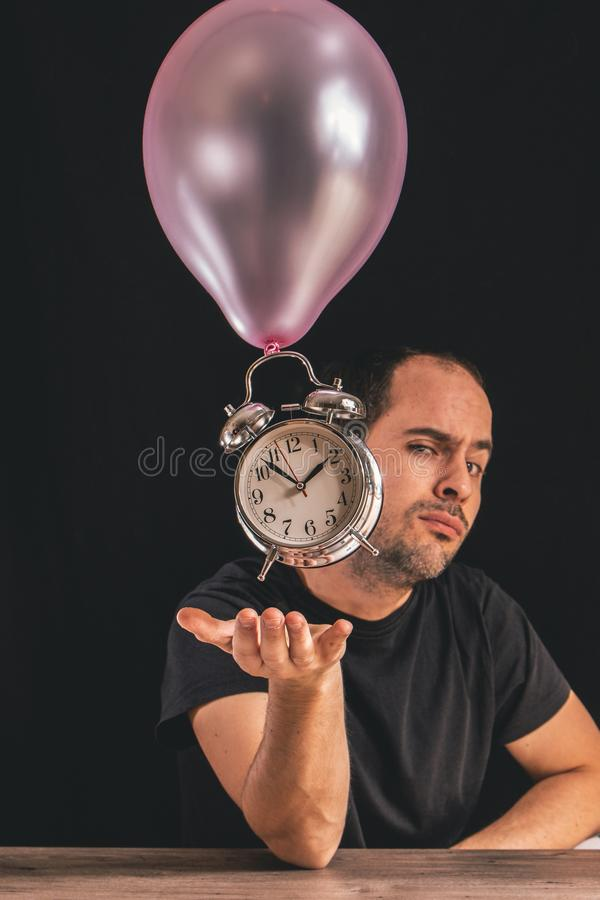 Time flies concept - picture of a man looking at the camera while placing his hand underneath an old metal clock royalty free stock images