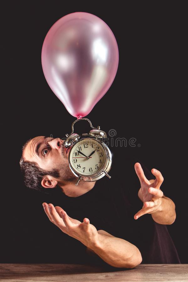 Time flies concept - picture of a man in panic trying to grab an old metal clock stock image
