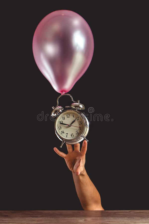 Time flies concept - picture of someone`s hand trying to reach an old metal clock that is attached to a pink balloon royalty free stock images