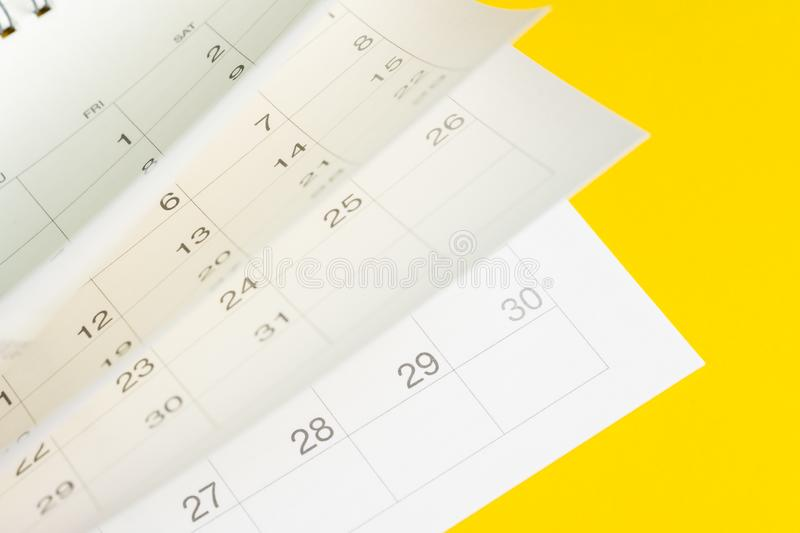 Time fly, season pass or reminder and appointment is coming event concept, white calendar turning pages with yellow background.  stock image