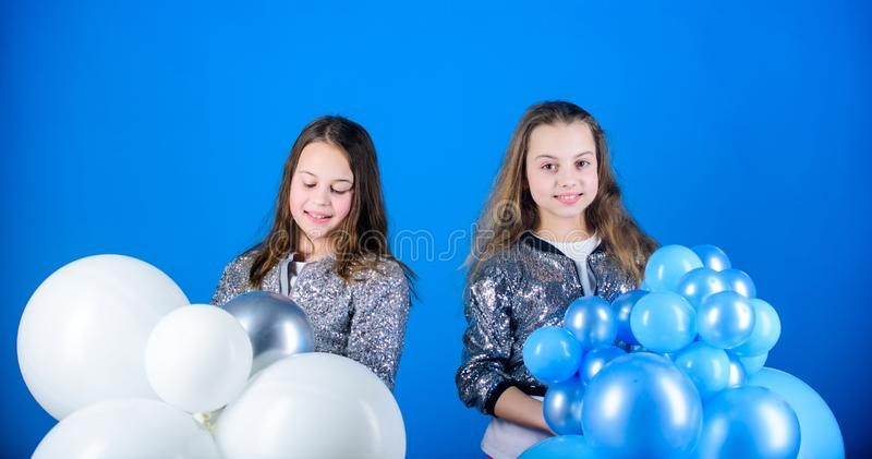 Time for fun. Adorable girls enjoy party time. Happy girls holding bunch of air balloons. Little girls having fun with royalty free stock photo