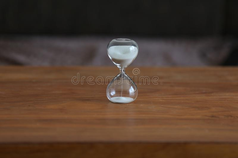 Time. Glass hourglass stands on the table. Glass hourglass stands on the table royalty free stock images