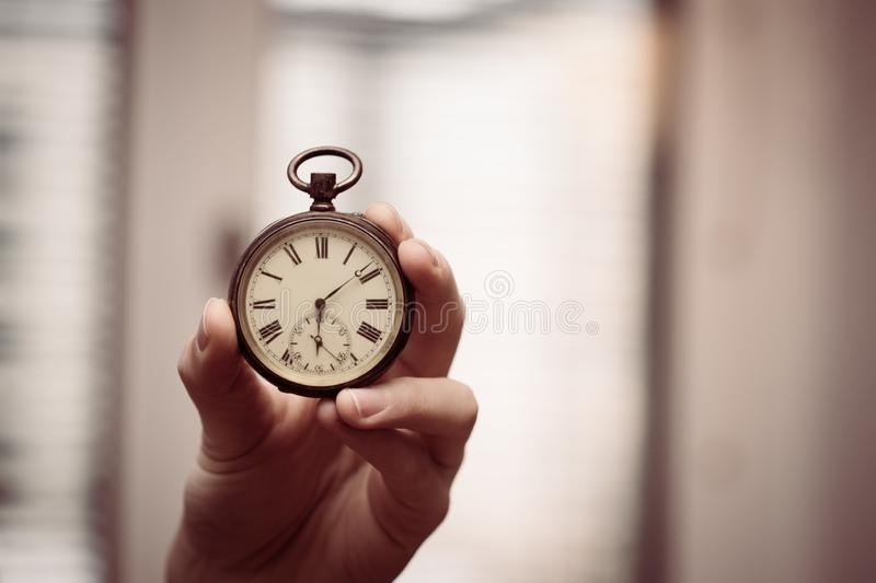 Time goes by: Man is holding a vintage watch in his hand, business context, copy space stock photography