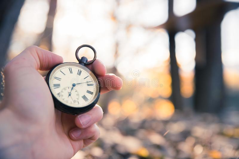 Time goes by: vintage watch outdoors, hand-held; wood and leaves stock images