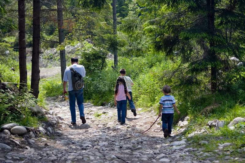 Time Hiking with Dad. Three children hiking along a mountain path with their Dad