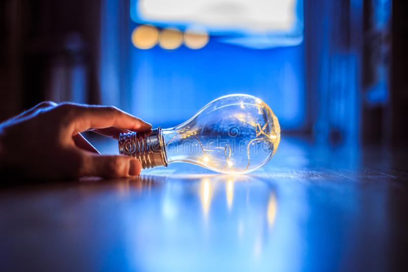 Time for ideas, inspiration and invention: Hands are holding a LED lightbulb. Hands are holding a LED lightbulb over the wooden floor. Symbol for ideas and stock photography