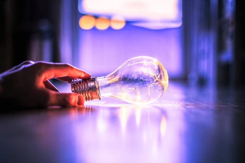 Time for ideas, inspiration and invention: Hands are holding a LED lightbulb. Hands are holding a LED lightbulb over the wooden floor. Symbol for ideas and royalty free stock image