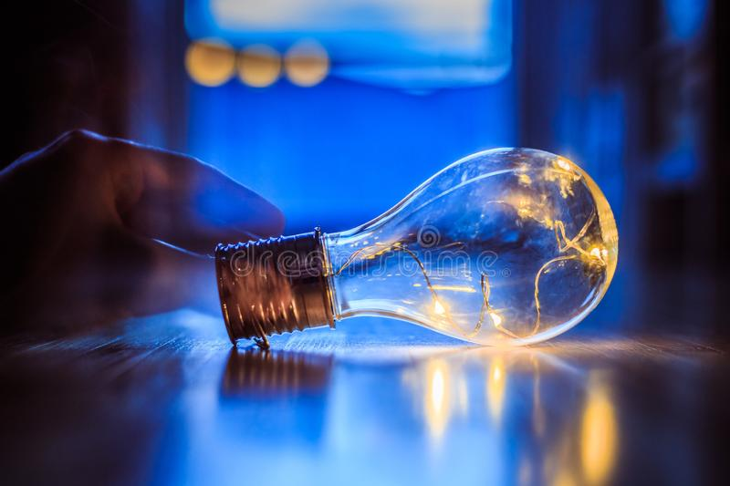 Time for ideas, inspiration and invention: Hands are holding a LED lightbulb. Hands are holding a LED lightbulb over the wooden floor. Symbol for ideas and stock image
