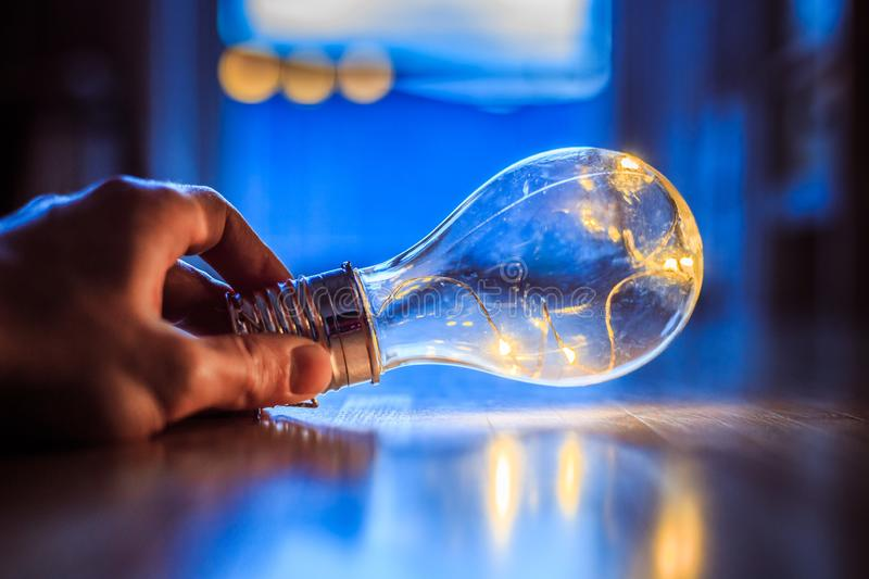 Time for ideas, inspiration and invention: Hands are holding a LED lightbulb. Hands are holding a LED lightbulb over the wooden floor. Symbol for ideas and stock photos