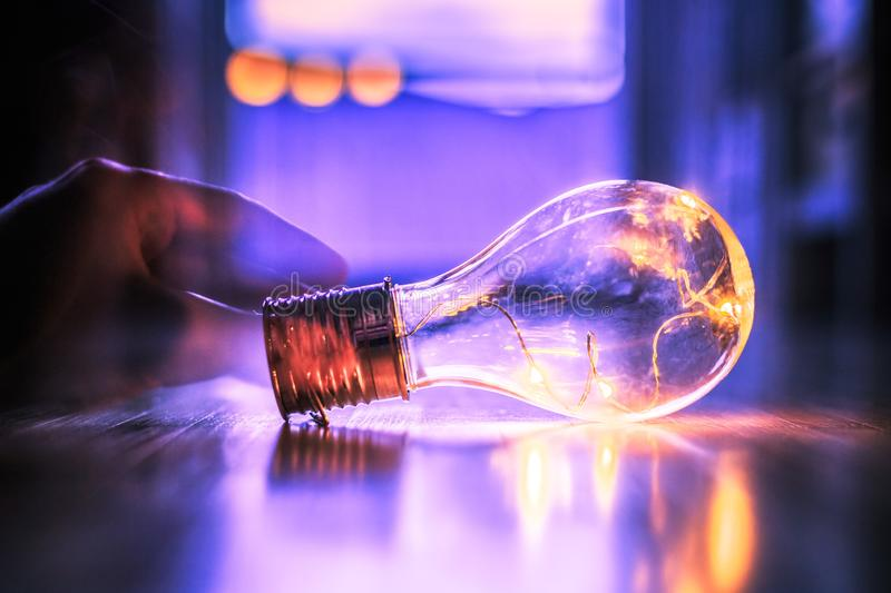 Time for ideas, inspiration and invention: Hands are holding a LED lightbulb. Hands are holding a LED lightbulb over the wooden floor. Symbol for ideas and stock photo