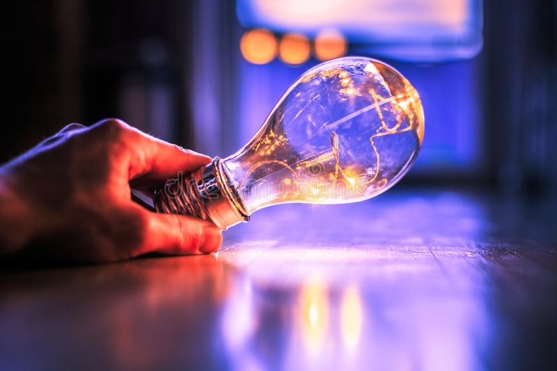 Time for ideas, inspiration and invention: Hands are holding a LED lightbulb. Hands are holding a LED lightbulb over the wooden floor. Symbol for ideas and royalty free stock photos