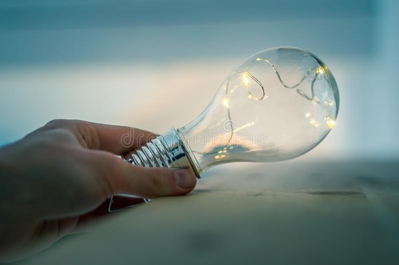 Time for ideas, inspiration and invention: Hands are holding a LED lightbulb. Hands are holding a LED lightbulb over the wooden floor. Symbol for ideas and royalty free stock photo