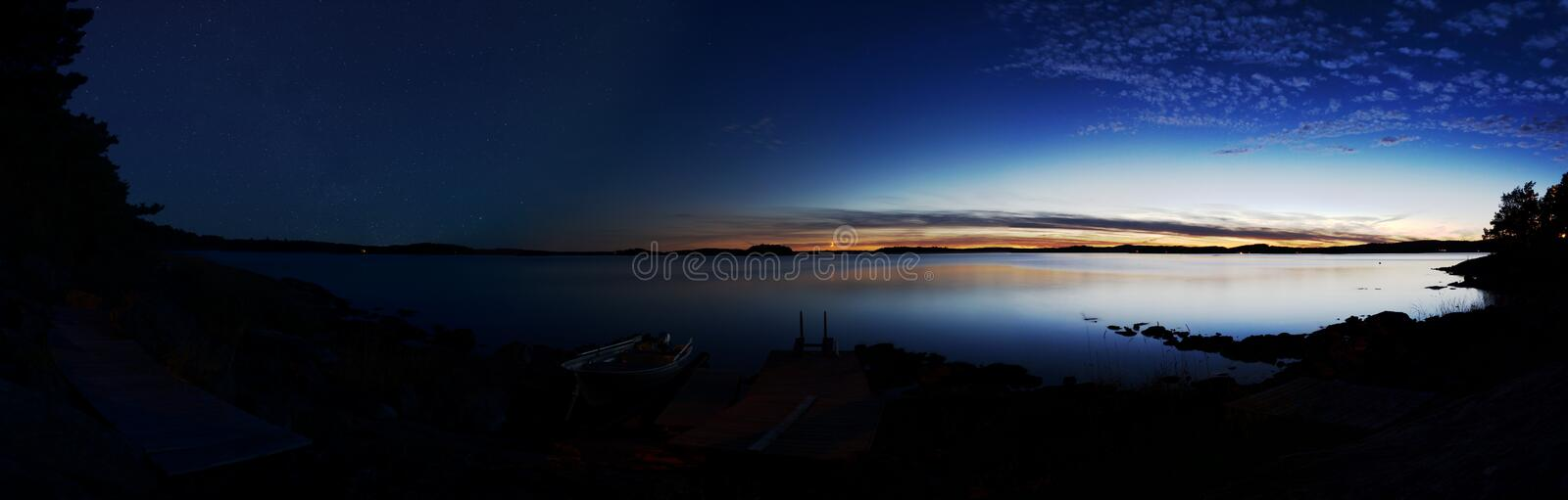 Time laps panorama: Lake with a sunset on the right and the night star sky on the left stock image