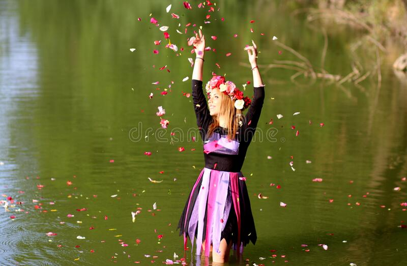 Time Lapse Photo Of Woman Standing In Green Body Of Water While Pouring Flower Petals On Air During Daytime Free Public Domain Cc0 Image
