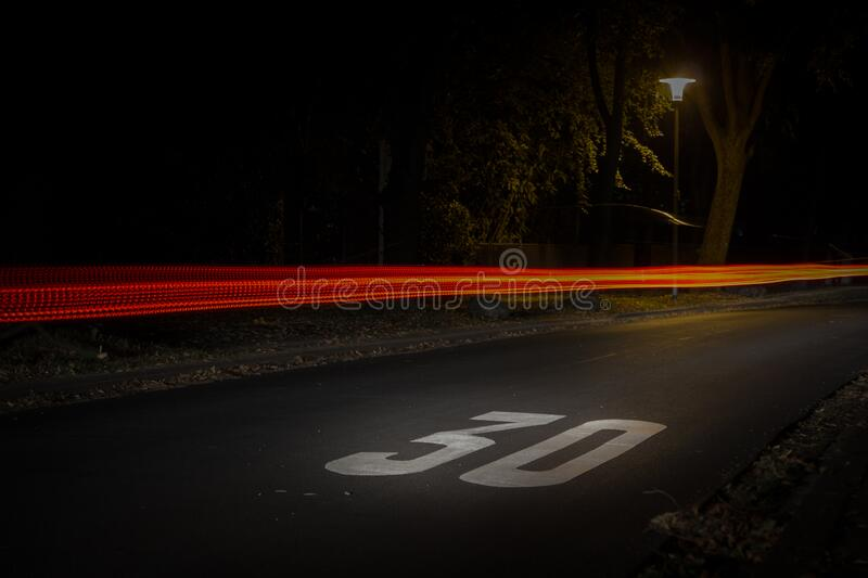 Time Lapse Photography of Red and Orange Light on Road With 30 Print on Nighttime stock photography