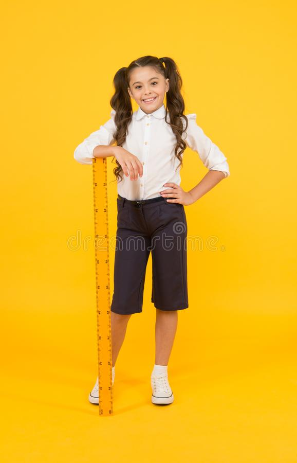 Time for learning. Small school child with ruler learning maths and geometry on yellow background. Little girl learning royalty free stock image