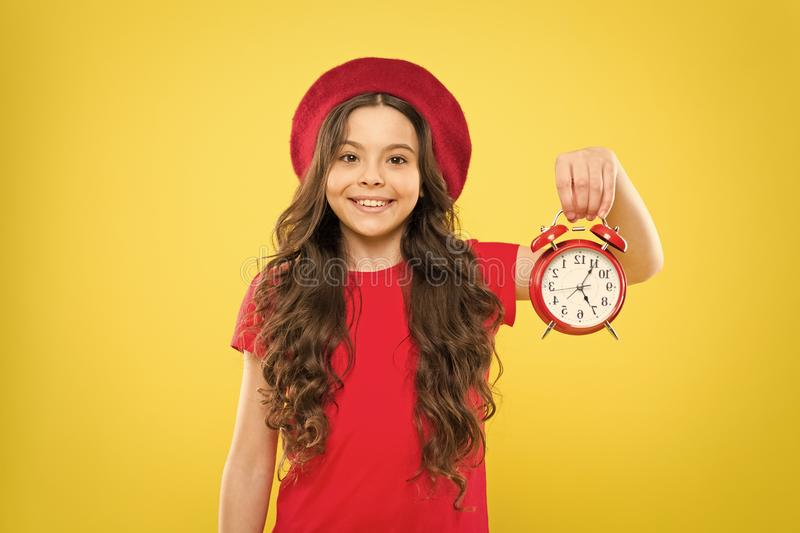 Time. little girl in french style hat. happy girl with long curly hair in beret. beauty hairdresser. child with alarm stock photo
