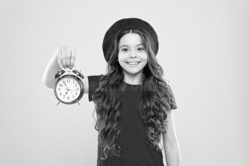 Time. little girl in french style hat. happy girl with long curly hair in beret. beauty hairdresser. child with alarm royalty free stock photography