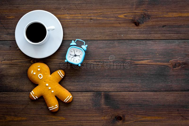 Hurry up concept. Gingerbread man near alarm clock on dark wooden background top view copy space. Time loss concept. Gingerbread man near alarm clock on dark royalty free stock image