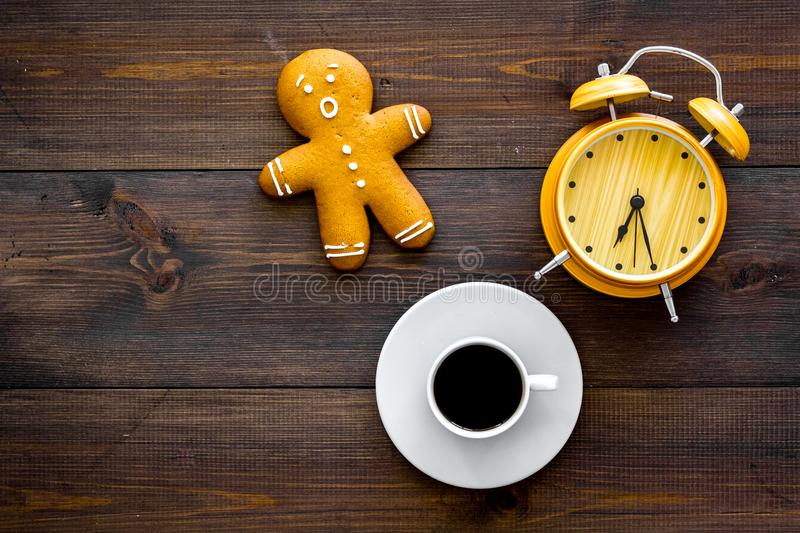 Time loss concept. Gingerbread man near alarm clock on dark wooden background top view space for text. Time loss concept. Gingerbread man near alarm clock on royalty free stock photos