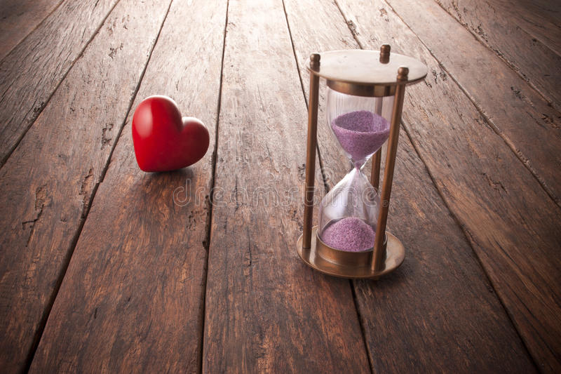 Time Love Clock Life Happiness Heart. A conceptual image about time and love with an hourglass and red love heart stock images