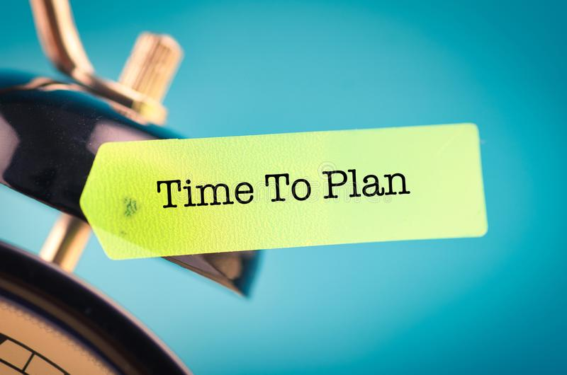 Close-up image of word TIME TO PLAN on yellow sticky paper and alarm clock royalty free stock image