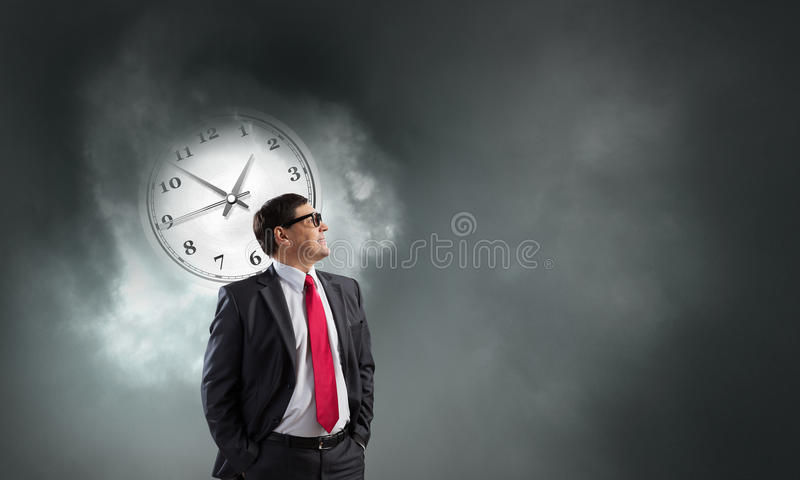Time management. Concept image. Middle-aged confident businessman in glasses and time concept royalty free stock images