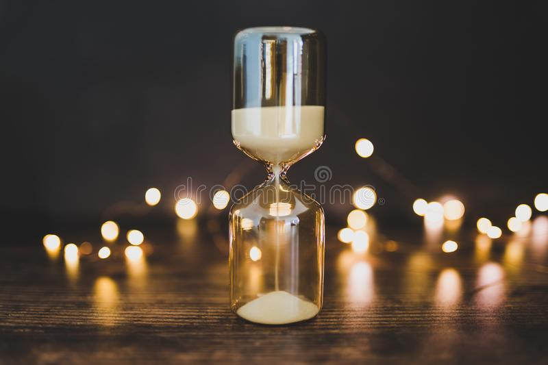 Time management hourglass surrounded by fairy lights bokeh. Time management conceptual image with hourglass surrounded by fairy lights bokeh on wooden office stock images