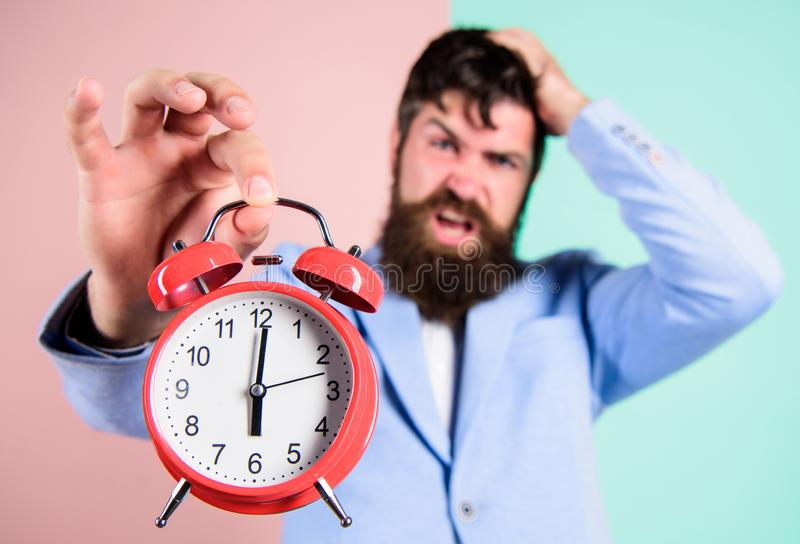Time management skills. How much time left till deadline. Time to work. Man bearded stressful businessman hold clock. Stress concept. Hipster stressful working stock images