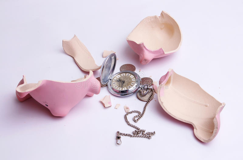 Time is money. Broken piggy bank with coins and watch isolated on white stock photo