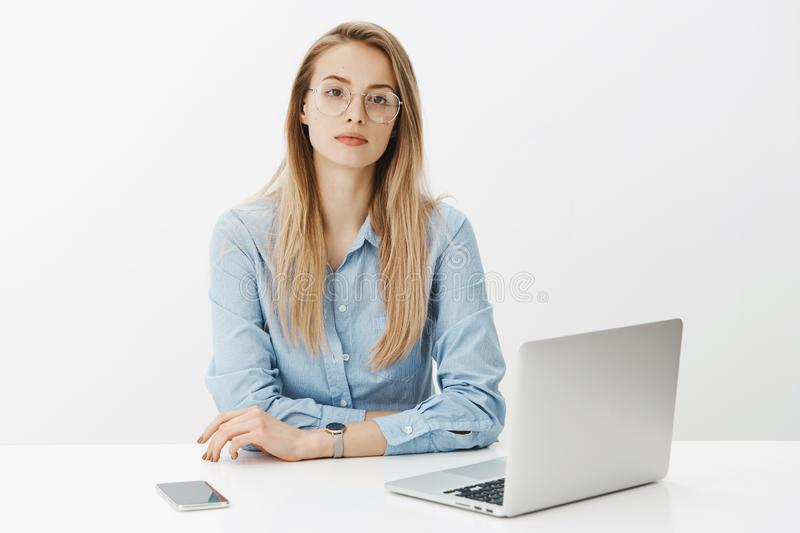 Time is money. Bossy self-assured successful female entrepreneur in blue-collar shirt and glasses sitting near laptop royalty free stock photography