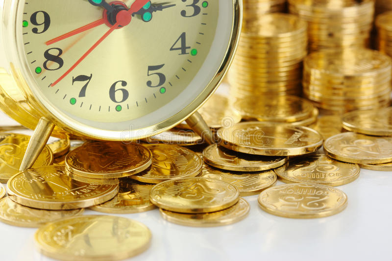 Time is money - clock dial and golden coins. Old-fashioned clock dial on golden coins background, time is money concept stock photo