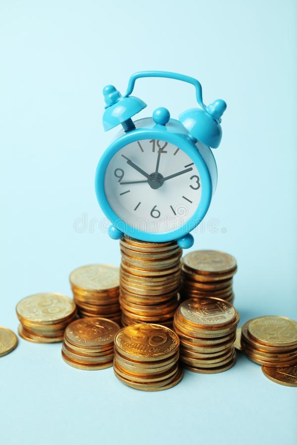 Time is money concept. Alarm clock and golden coins. Financial option of cash investment stock image