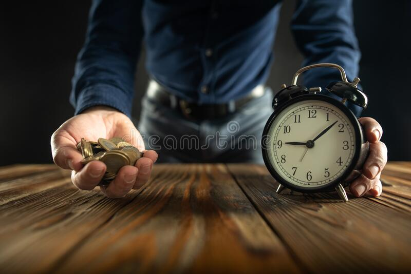 Time is Money Concept with Businessman with Alarm Clock and Handful Coins stock image