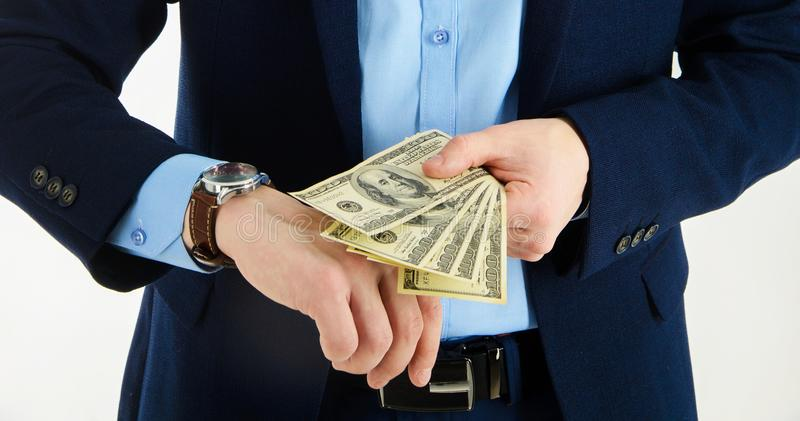 Time is money concept. Businessman looking on watch and holding money stack in hand. Closeup. Isolated on white.  stock photo
