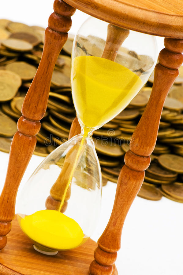 Time is money concept - hourglass. And coins stock photo