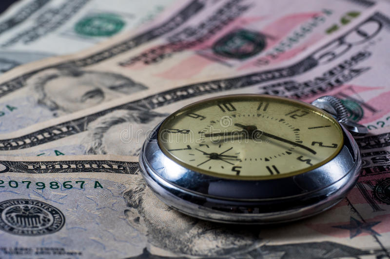 Time is Money - concept image. Clock watch on money - fifty dollar bills - concept image - time is money - growth over time stock photo