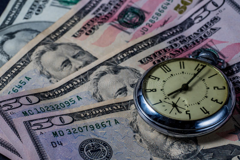 Time is Money - concept image. Clock watch on money - fifty dollar bills - concept image - time is money - growth over time stock image
