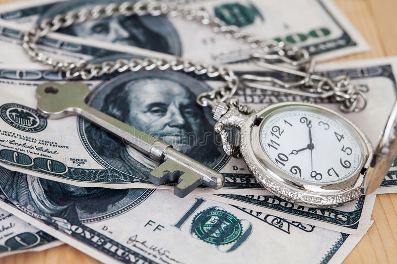 Time and money concept image - old silver pocket watch. And US currency .vintage style light and ton stock photos
