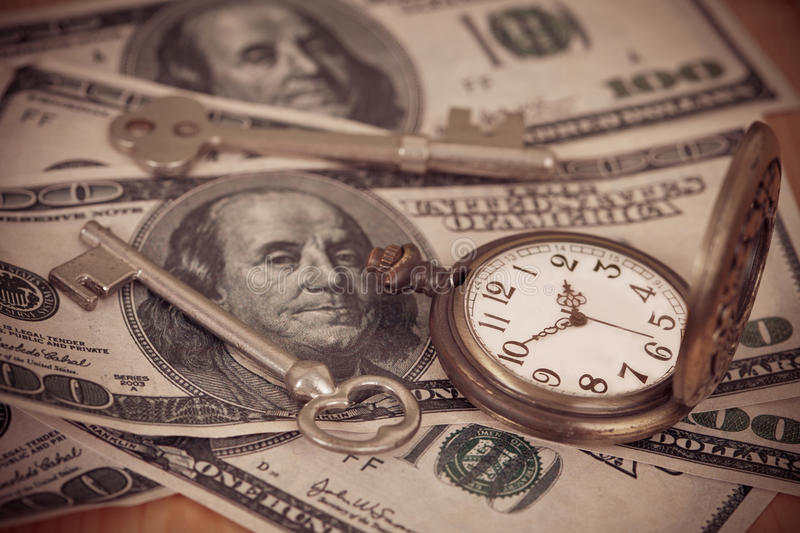 Time and money concept image - old silver pocket watch. And US currency .vintage style light and tone stock images