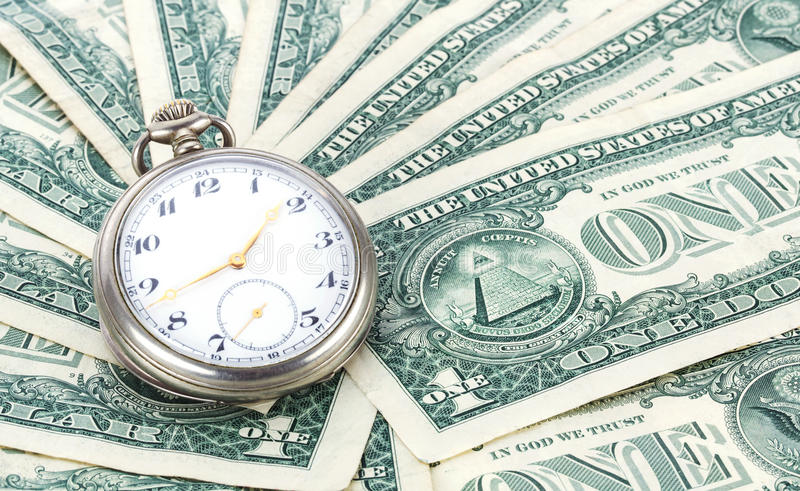 Time is money. Concept, old pocket watch laying on a pile of on dollar bills stock images