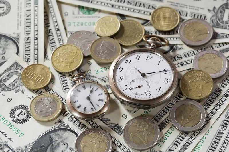 Time is money finance concept with old vintage clocks, dollar bills and euro coins.  stock photos