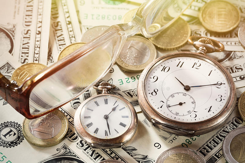 Time is money finance concept with old vintage clocks, dollar bills, euro coins and glasses.  royalty free stock photography