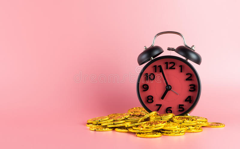 Time is money, gold on alarm clock on pink stock image